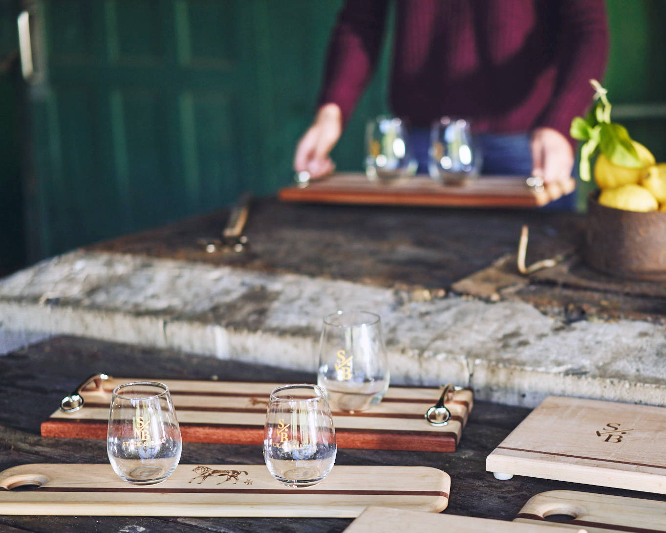 Outdoor display of entertaining serving boards & stemless wine glass with Stick & Ball Logo & Signature Polo Pony