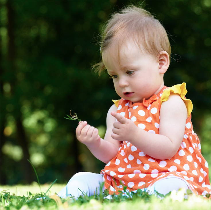bagy girl in a red dress with white polka dots sitting on green grass