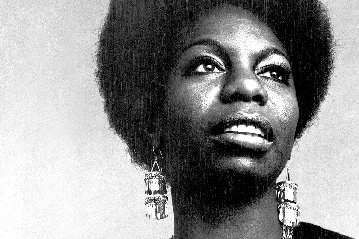 Black and white image of nina simone, wearing large earrings and her hair in an afro, looking to the distance.
