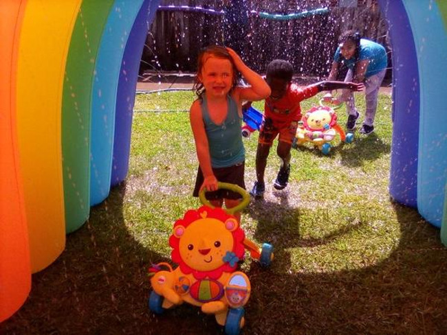 Children pushing toys through an inflatable rainbow that has water streaming from it