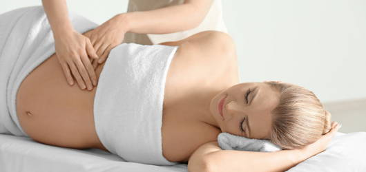 relaxed pregnant woman being massaged