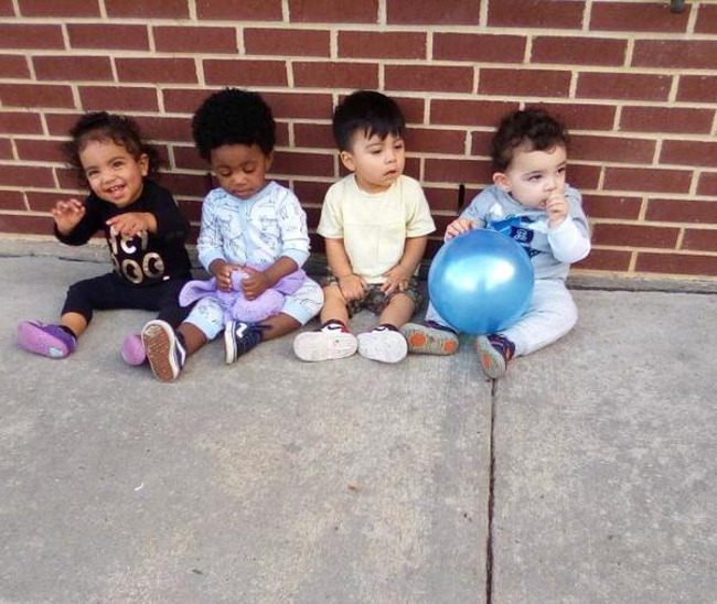Four toddlers sitting on the ground. One holds a purple duck and another holds a blue ball