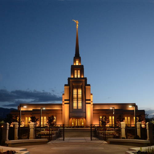 Evening photo of the Gila Valley Temple glowing against a dark blue sky.
