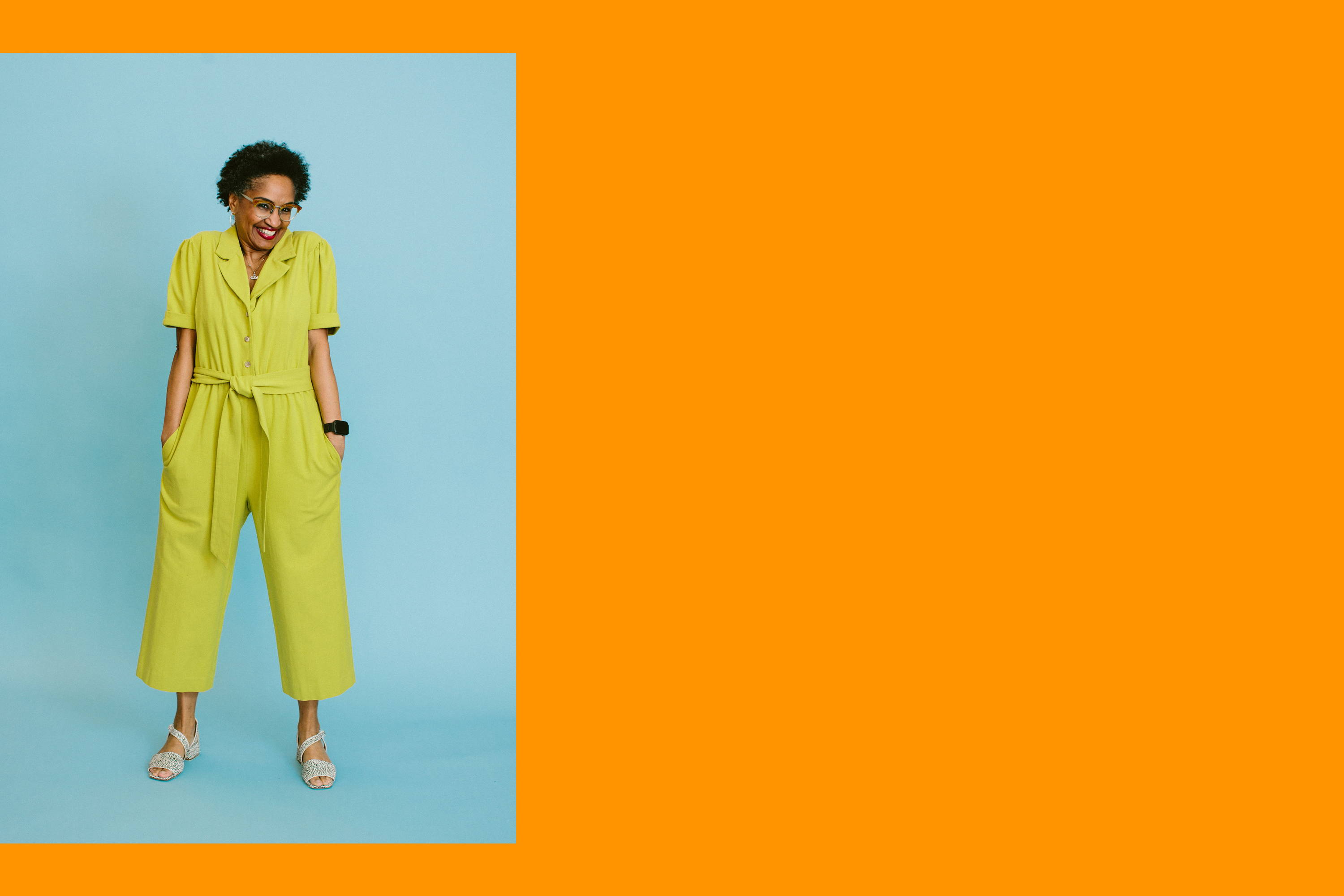 valerie wears the olivia jumpsuit in chartreuse. she is standing with her hands in her pockets in front of a baby blue background. the photo is colorblocked on an orange background.