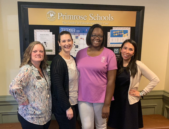 Ms. Jasmine Baker poses with her colleagues in the hallway