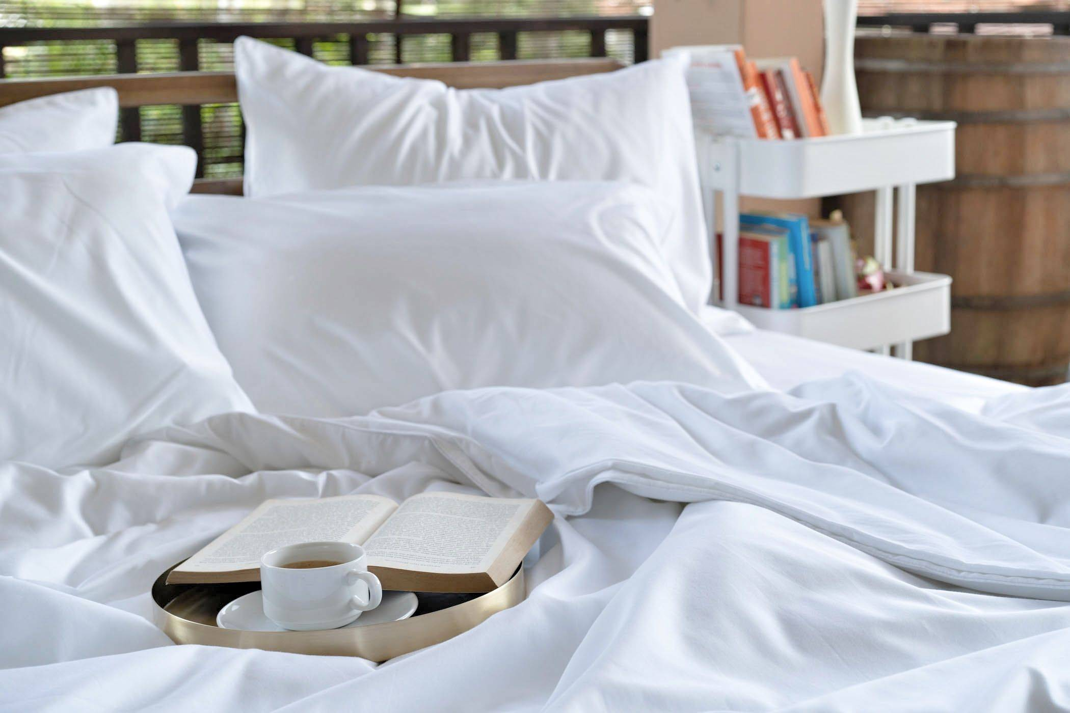 Featuring Weavve's Cloud White Cotton Deluxe Set with 1 fitted sheet, 1 duvet cover, 4 pillow cases and 2 bolster cases, with a tray with a coffee mug and book placed on top of it