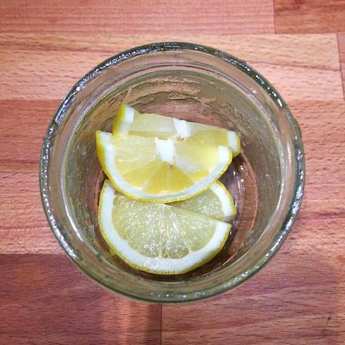 leeres Honigglas mit Zitronenscheiben