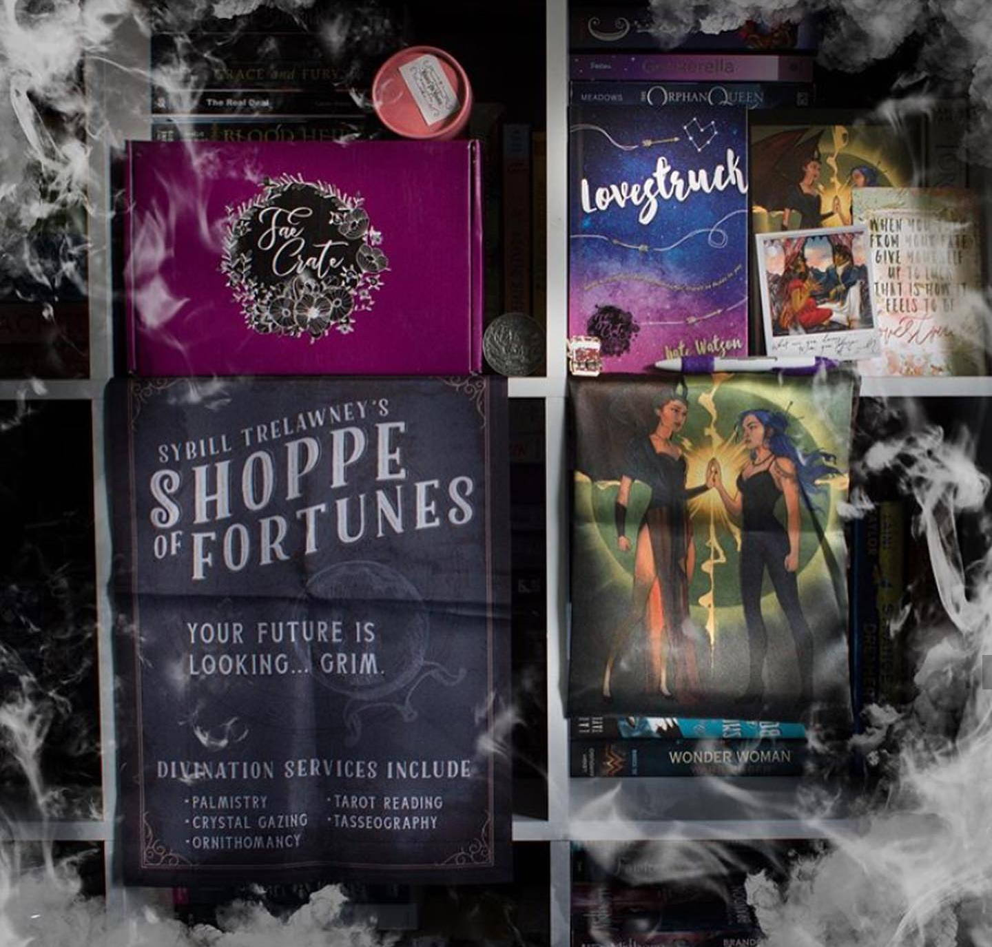 May 2019 Fate's Design box theme included Fae Crate Exclusive Cover of Lovestruck by Kate Watson, E-Book Download of Imber by @tyffany.h, Sybill Trelawney's Shoppe of Fortunes Flag, A Darker Shad of Magic Collector's Coin, TBR Pen, Daughter of Smoke and Bone Slip, Magnus Themed Incense, The Wrath and the Dawn Polaroid, Furyborn Enamel Necklace Charm, and Eragon Shirt for Seelie and Solitary Fae boxes only.