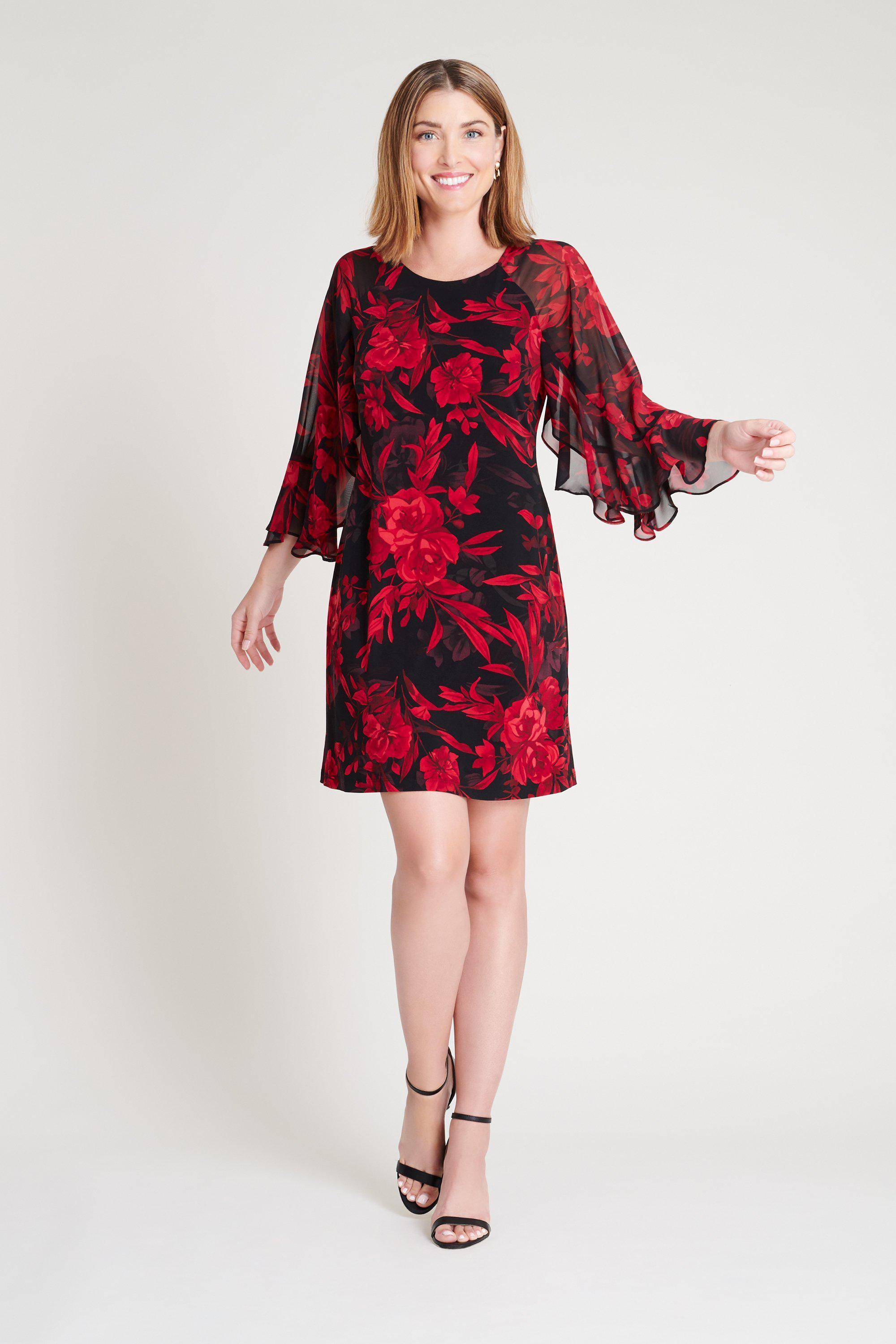 young short haired blonde woman in chiffon raglan sleeve short red and black floral connected apparel dress