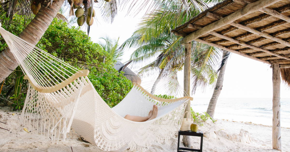 White hammock on beach at Olas resort in Tulum Mexico