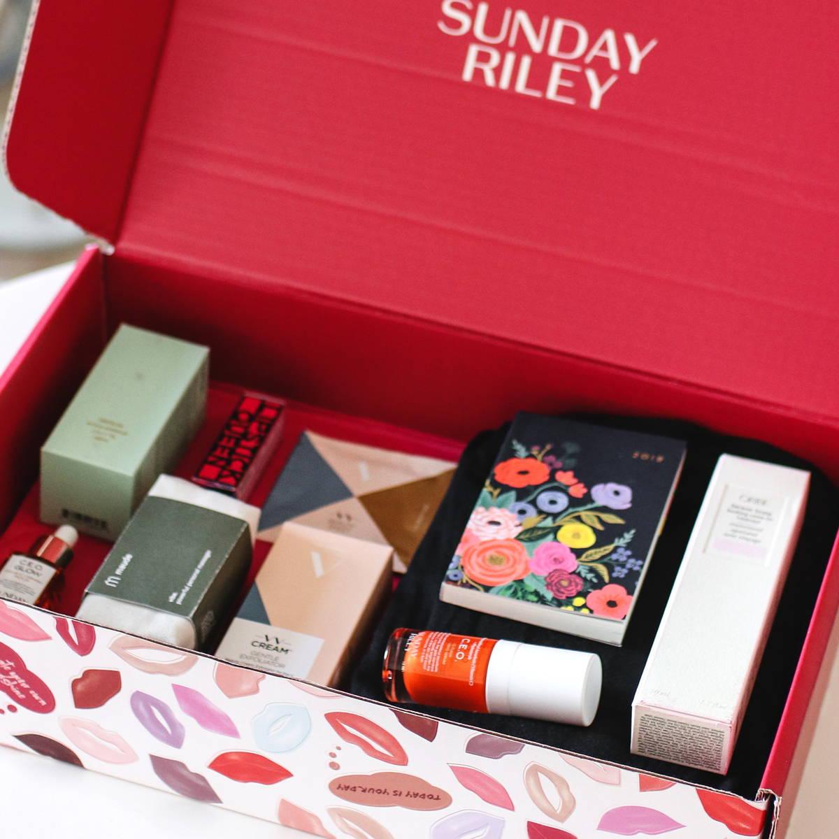 The Love Box subscription box by Sunday Riley, opened exposing the items/ products contained within. Products include, C.E.O. Glow Vitamin C + Turmeric Face Oil 15 ml/0.5 fl oz, Lipstick Queen, and a Maude Vibe personal massager to name a view.