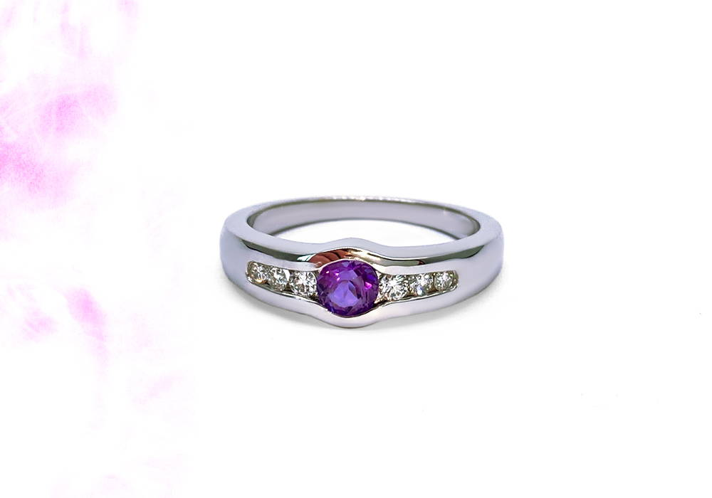 White gold ring with an amethyst as main stone and 3 small diamonds set on each side