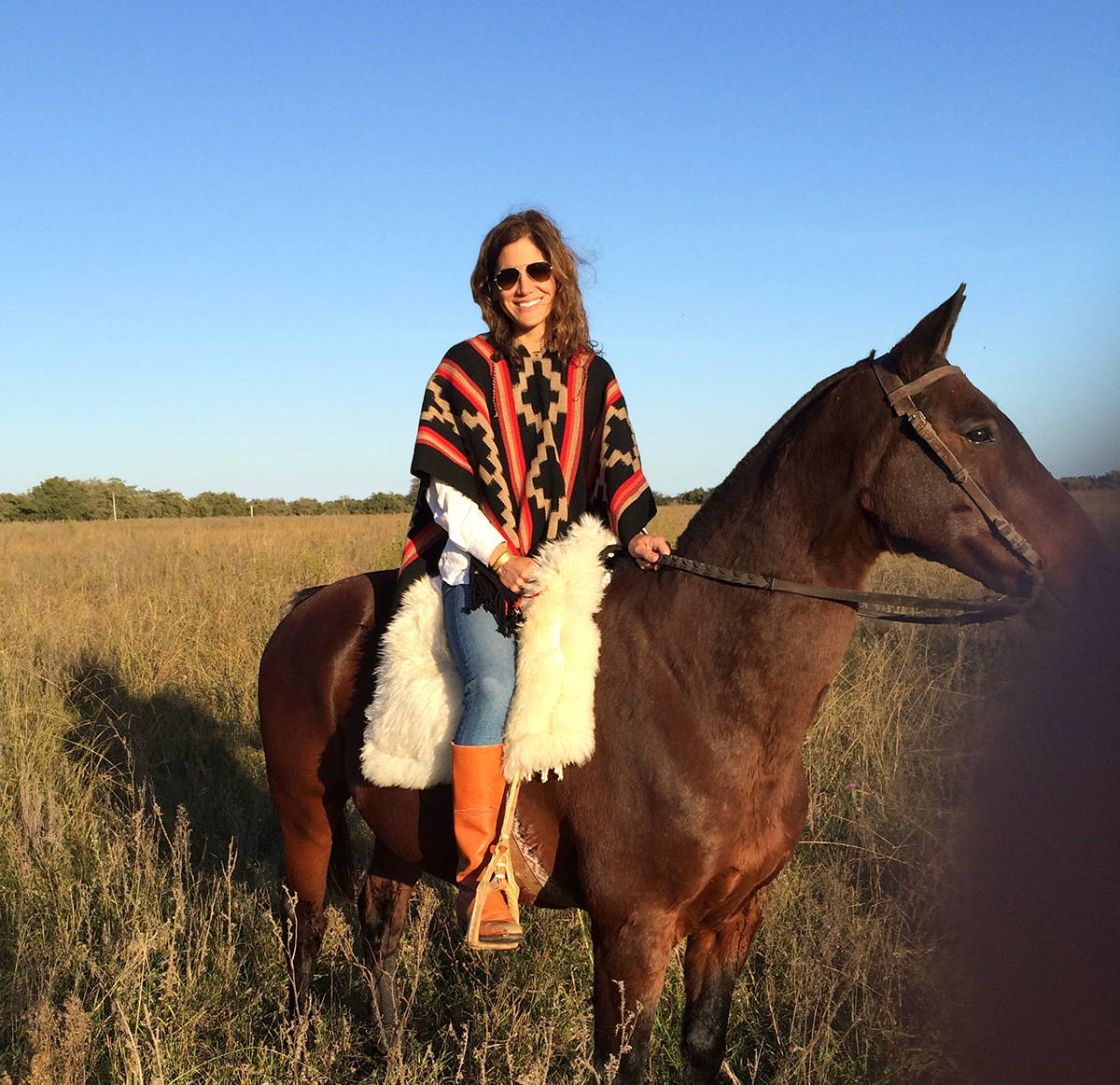 Elizabeth sits atop a horse wearing an Argentine poncho.
