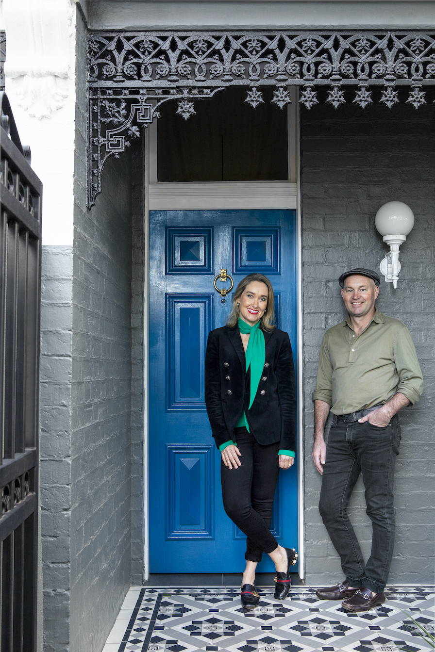 Husband and wife, Matt & Kate standing outside their blue front door