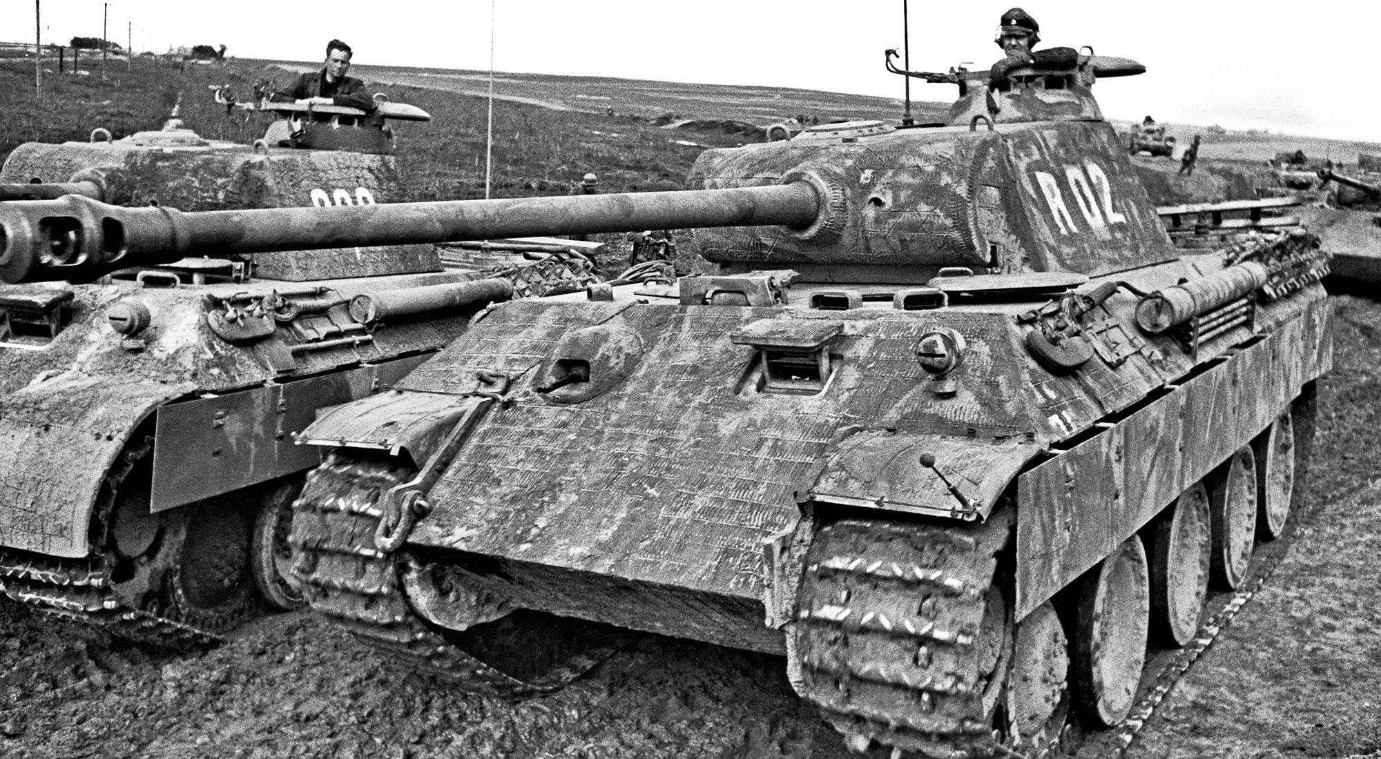 A crew man from Nicolussi-Leck's Panther 800 watches as Muhlenkamp's Panther R02 rumbles past Kovel, 1944.