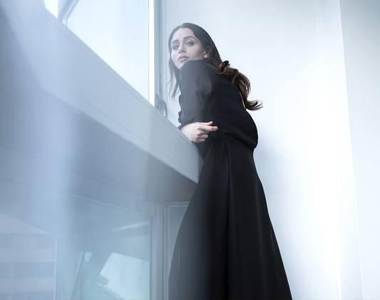a woman wears a black dress leaning against window