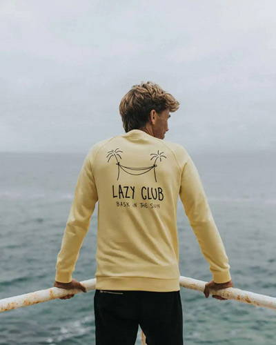 Man standing facing the sea with a yellow organic cotton sweatshirt with palm tree illustration printed on the reverse
