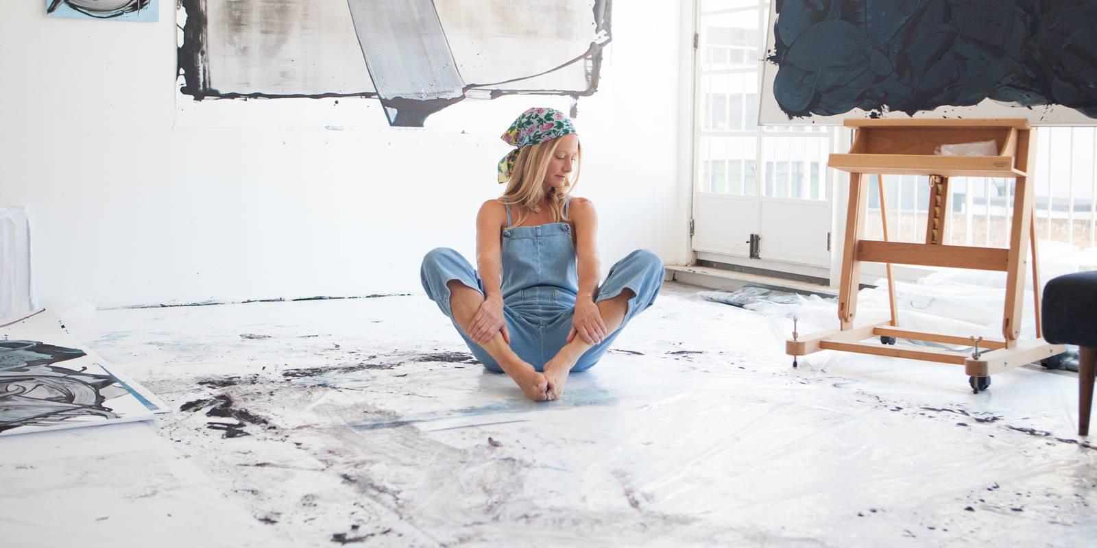 Lisa Oxenham sat on a white painted floor