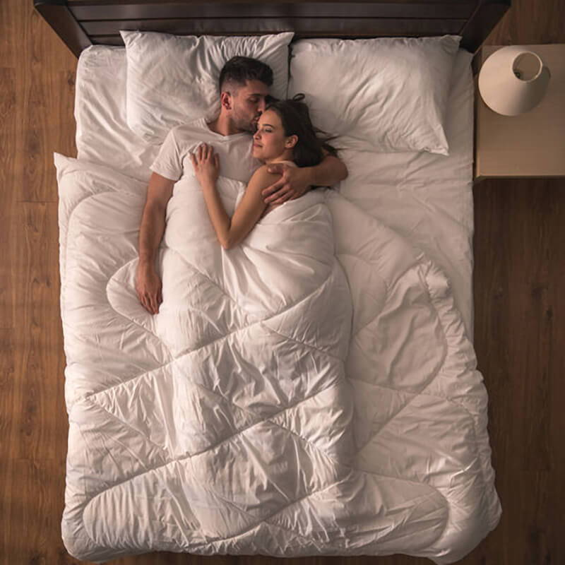 couple waking up rested and happy in bed