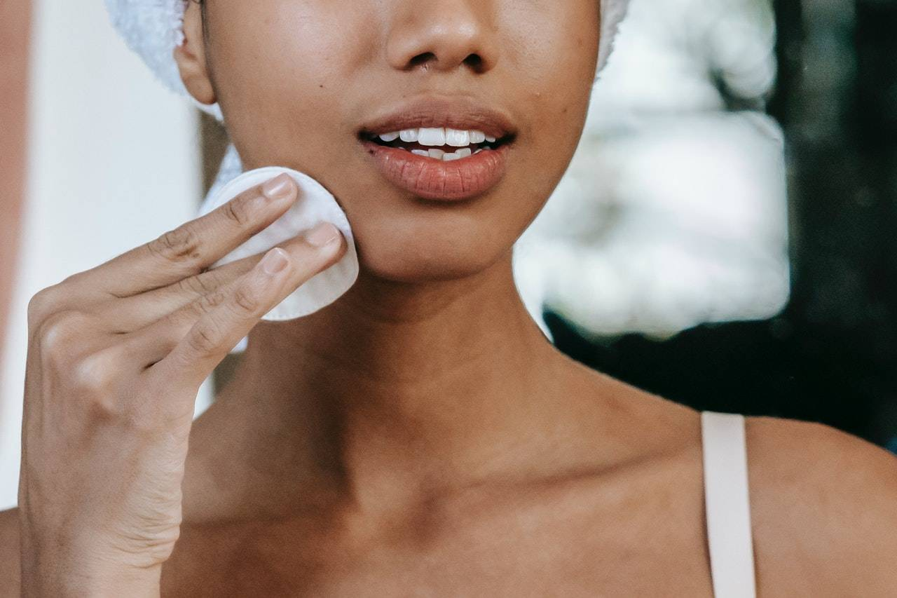 Crop woman cleaning face with cotton pad
