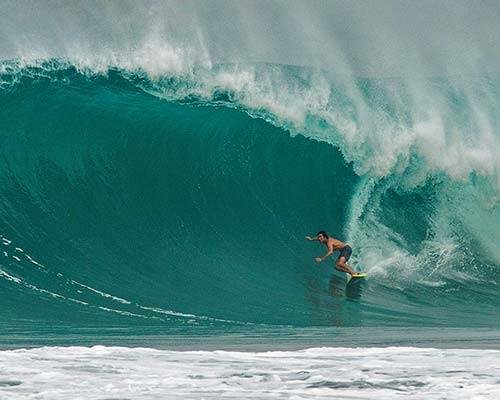 Greg Long wearing Patagonia board shorts crushing a 20ft barrel surfing