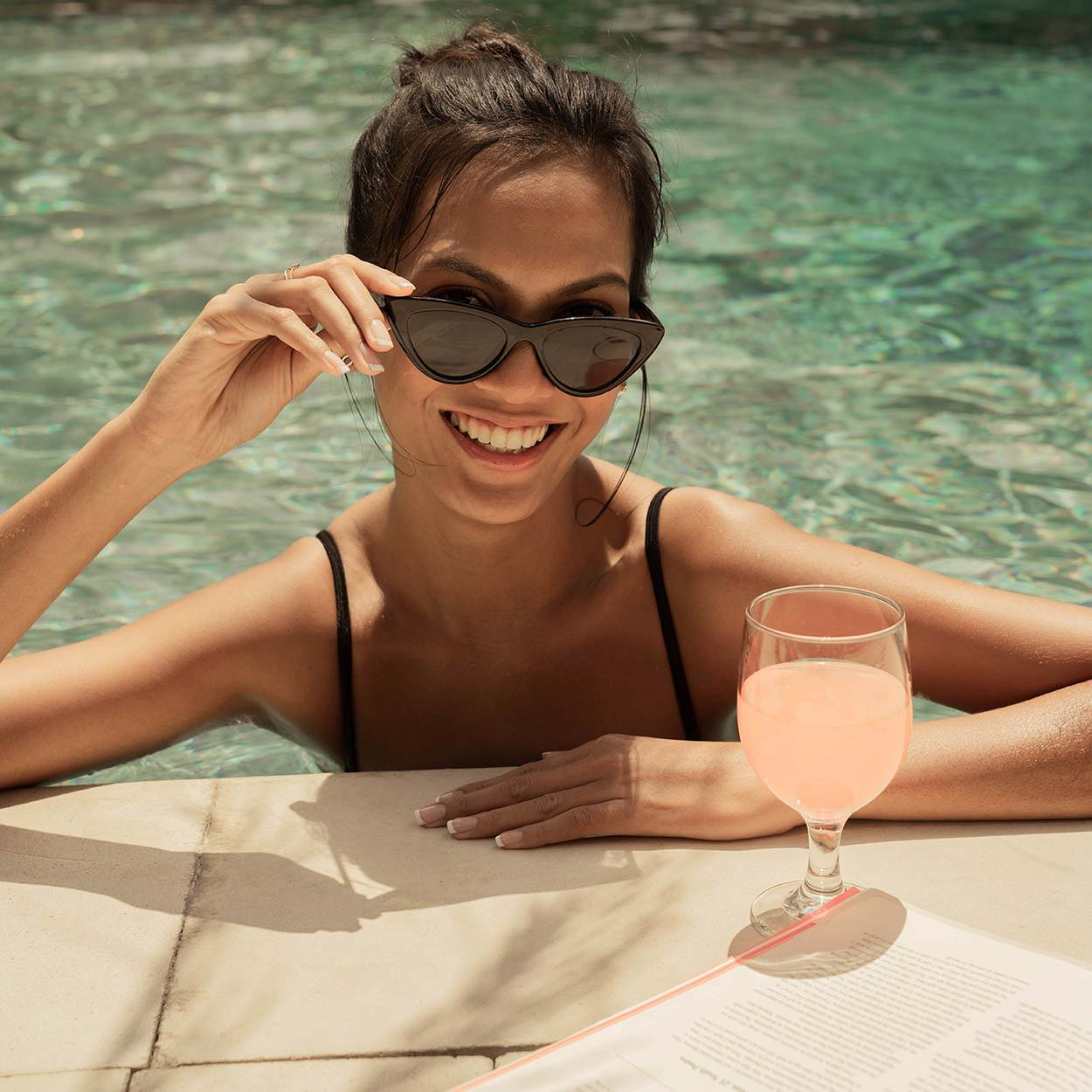 Woman smiling in a pool with a glass of rosé