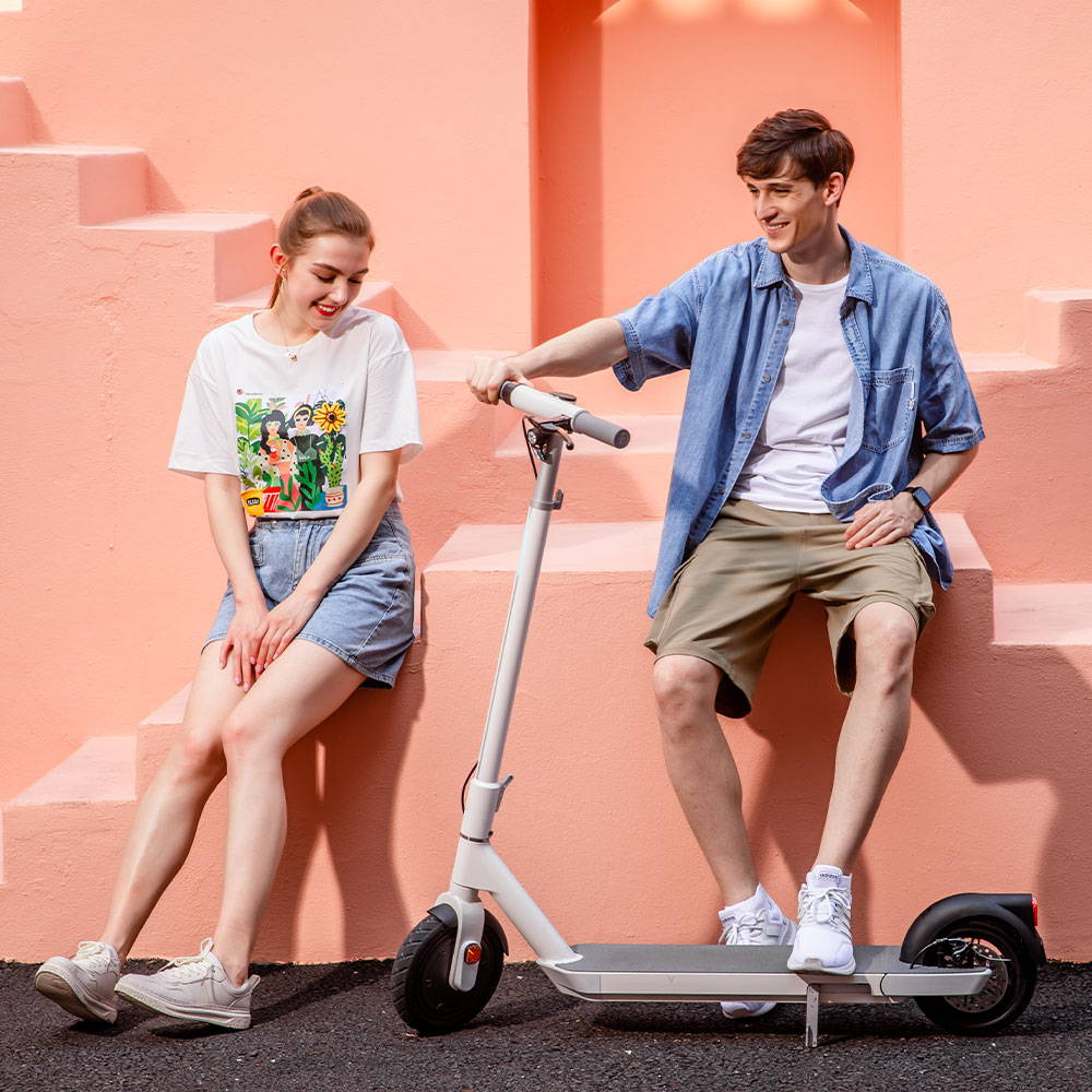 okai neon electric scooter couple smiling next to scooter