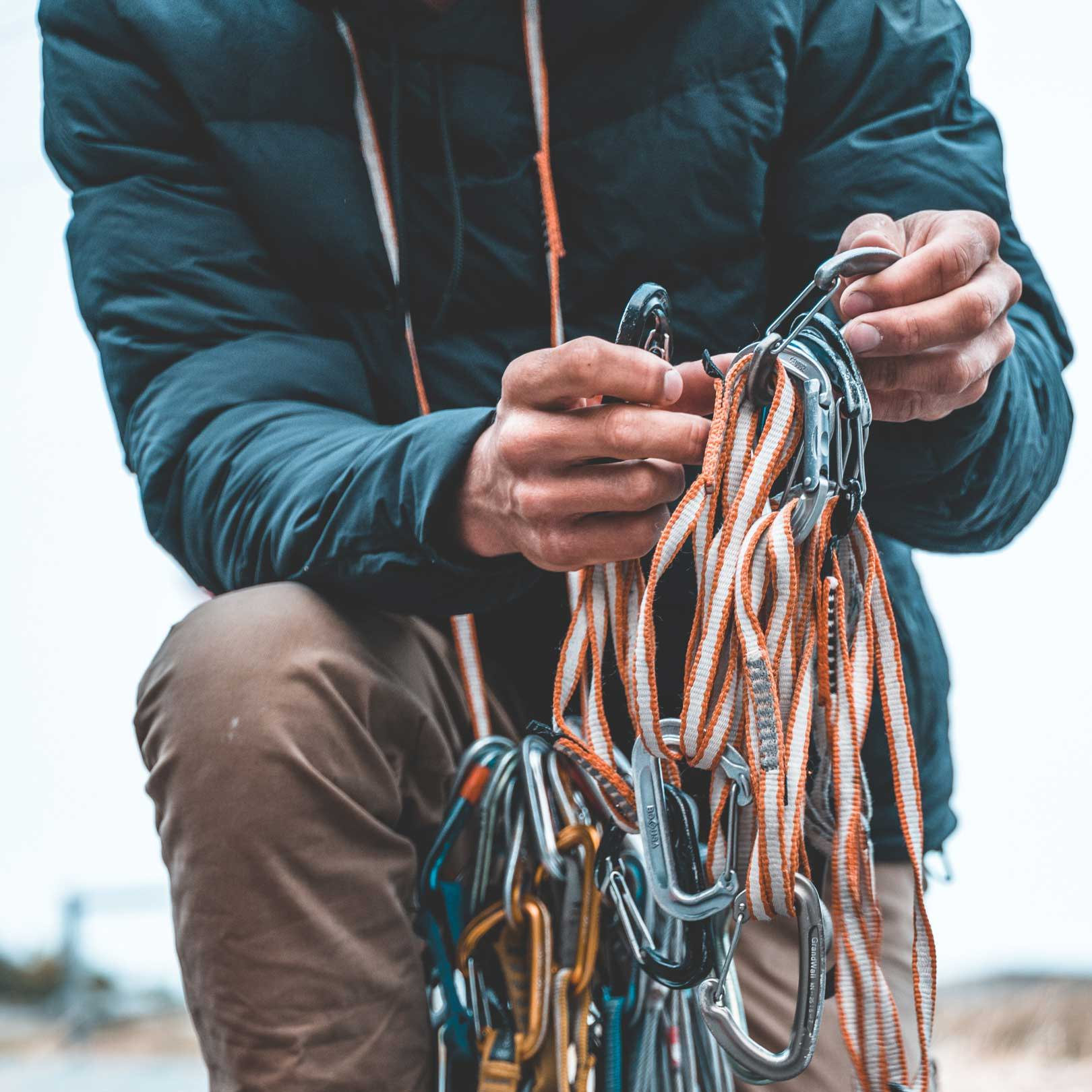 Man organizing climbing gear while wearing Robson Down Hoody