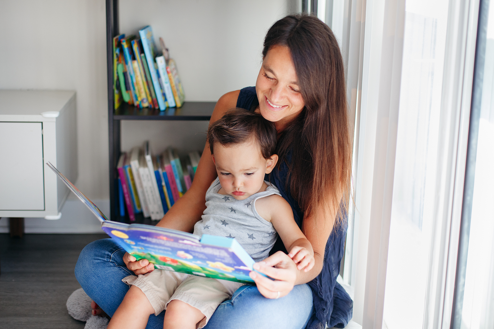 Mother with son boy sitting on floor at home and reading book together.