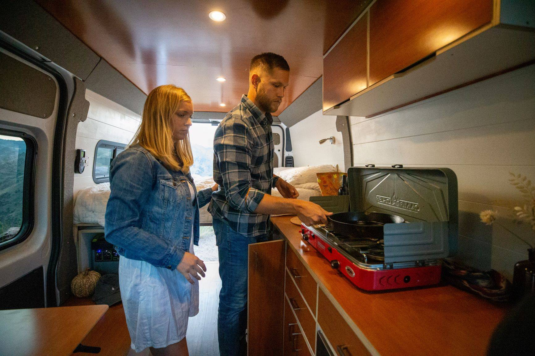 The Bivy - Sprinter 144 / ProMaster 136 Van Conversion - Man and Woman Cooking on Camp Stove in Kitchen Area - The Vansmith