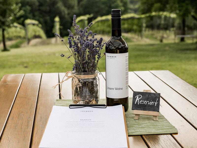 Buschenschank-Tisch mit Reserviert-Schild, Wein und Lavendel-Deko.