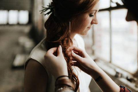 photo of a bridesmaid having her hair braided