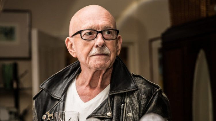 An older man with glasses and a white moustache wearing a battered leather jacket.
