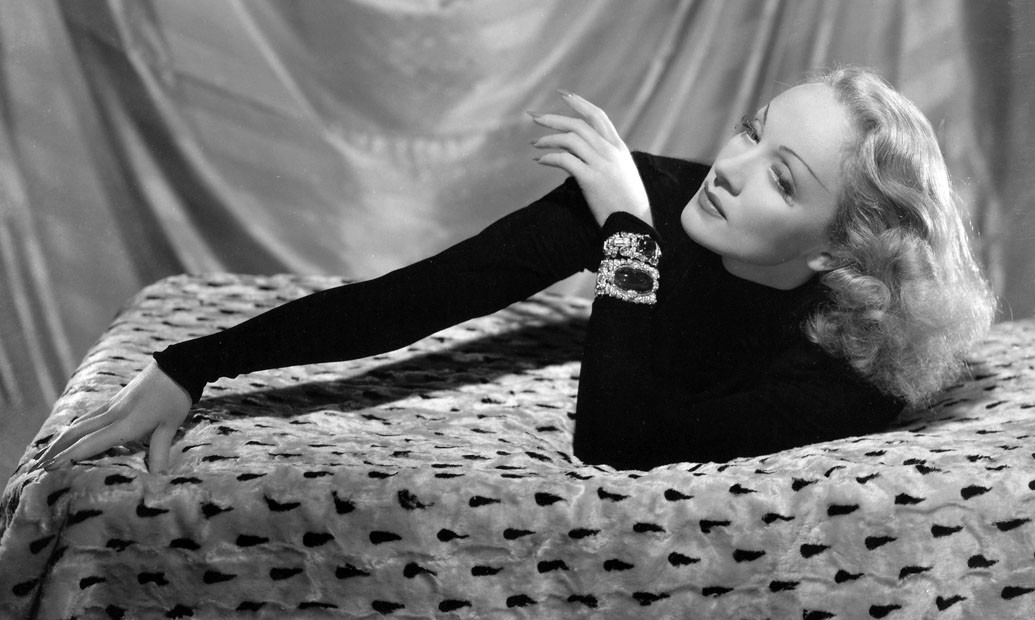 Marlene wearing a dark long sleeve shirt, laying on a bed with her hand stretched out and his hair wavy and down.