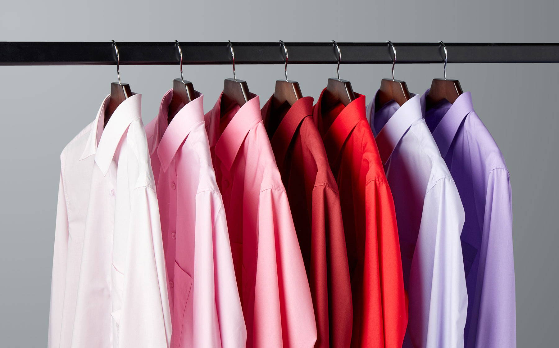 Pink and red shirts hanging on rail