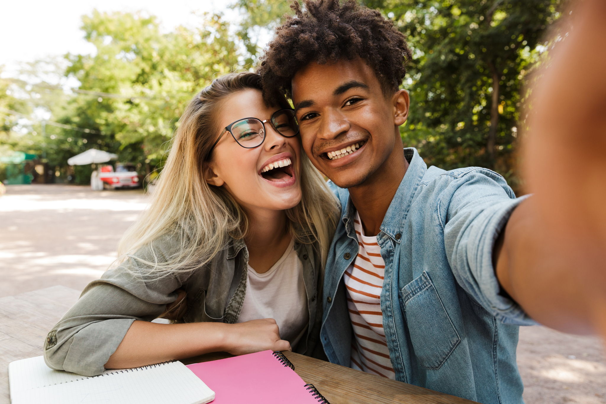 Image of a young attractive multi ethnic couple smiling and taking a selfie together. They are sitting on a bench in a park working on a project together.