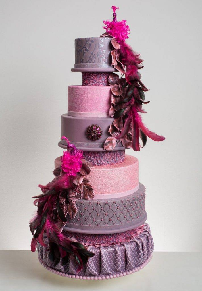 Elegant pink and purple nine tiered wedding cake with feather details made by the team at House of Clarendon in Lancaster, PA