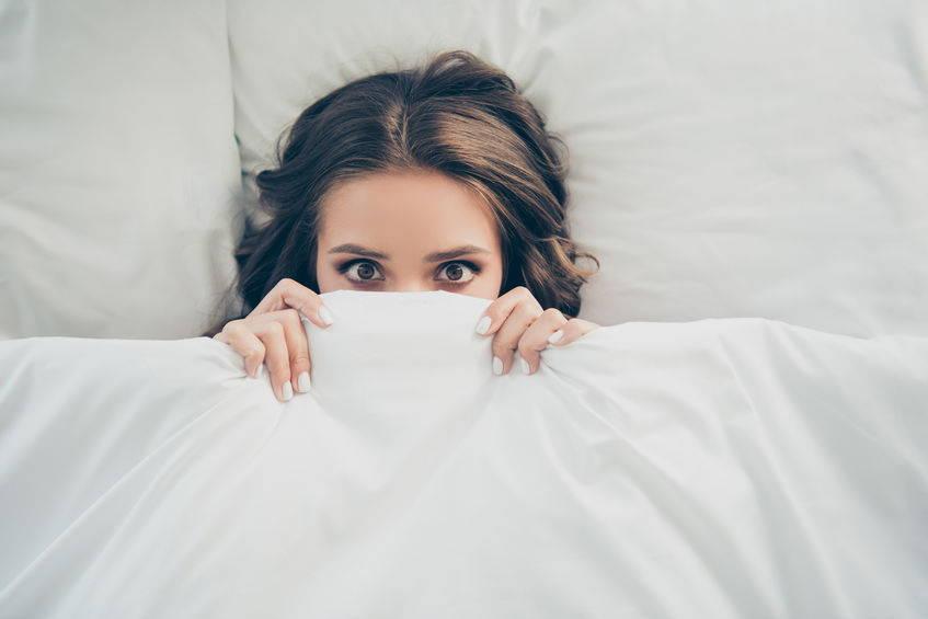 Girl hiding under bedsheet
