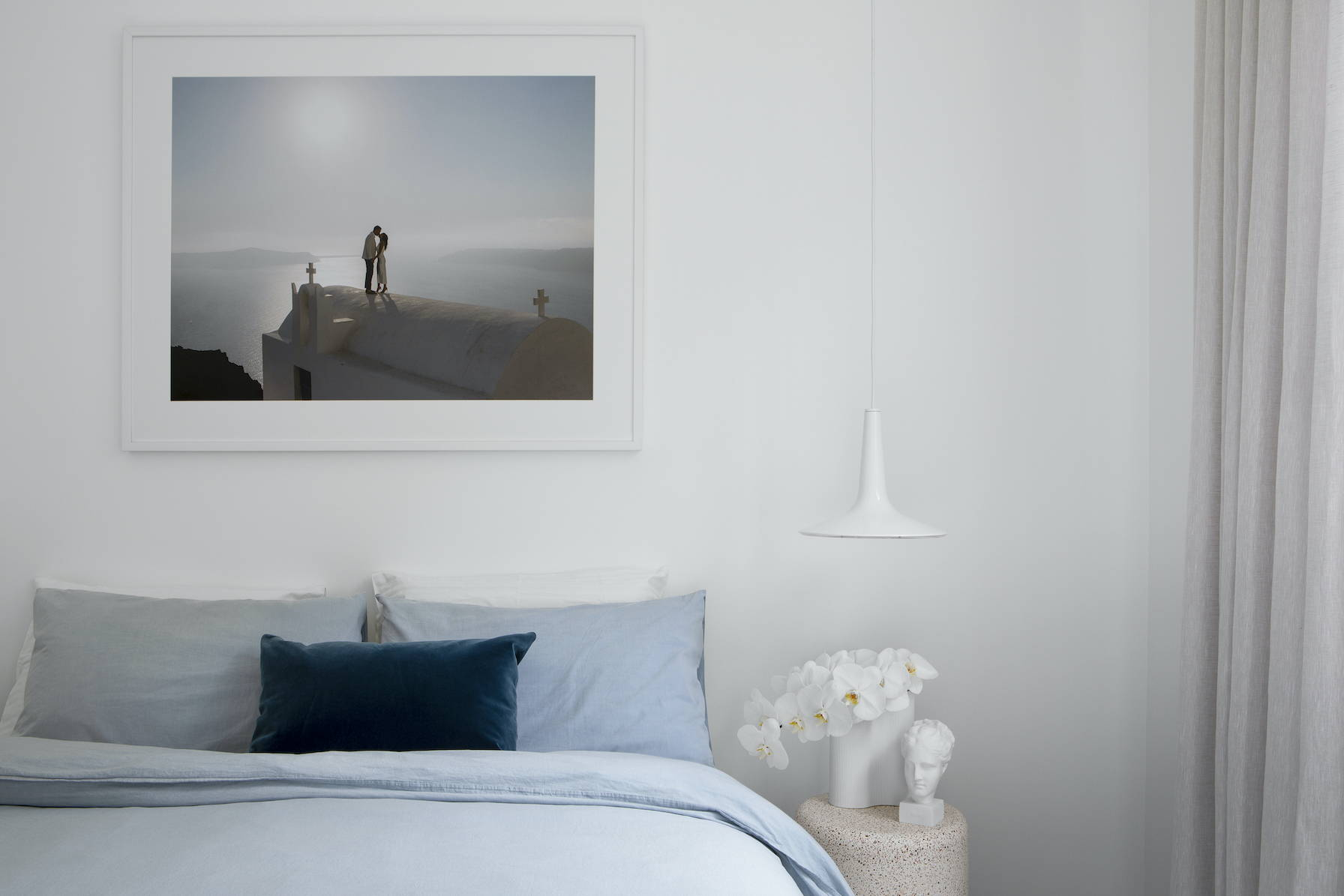 Wedding photography framed and hanging above a beautiful bedroom setting