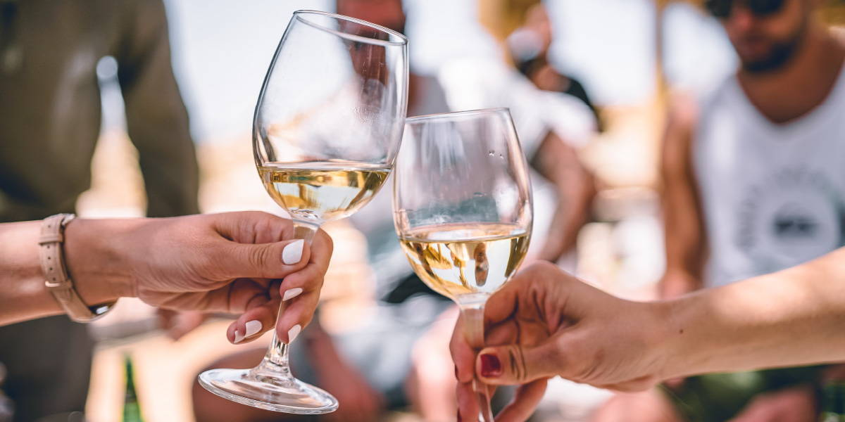 Two filled glasses of white wine toasting.