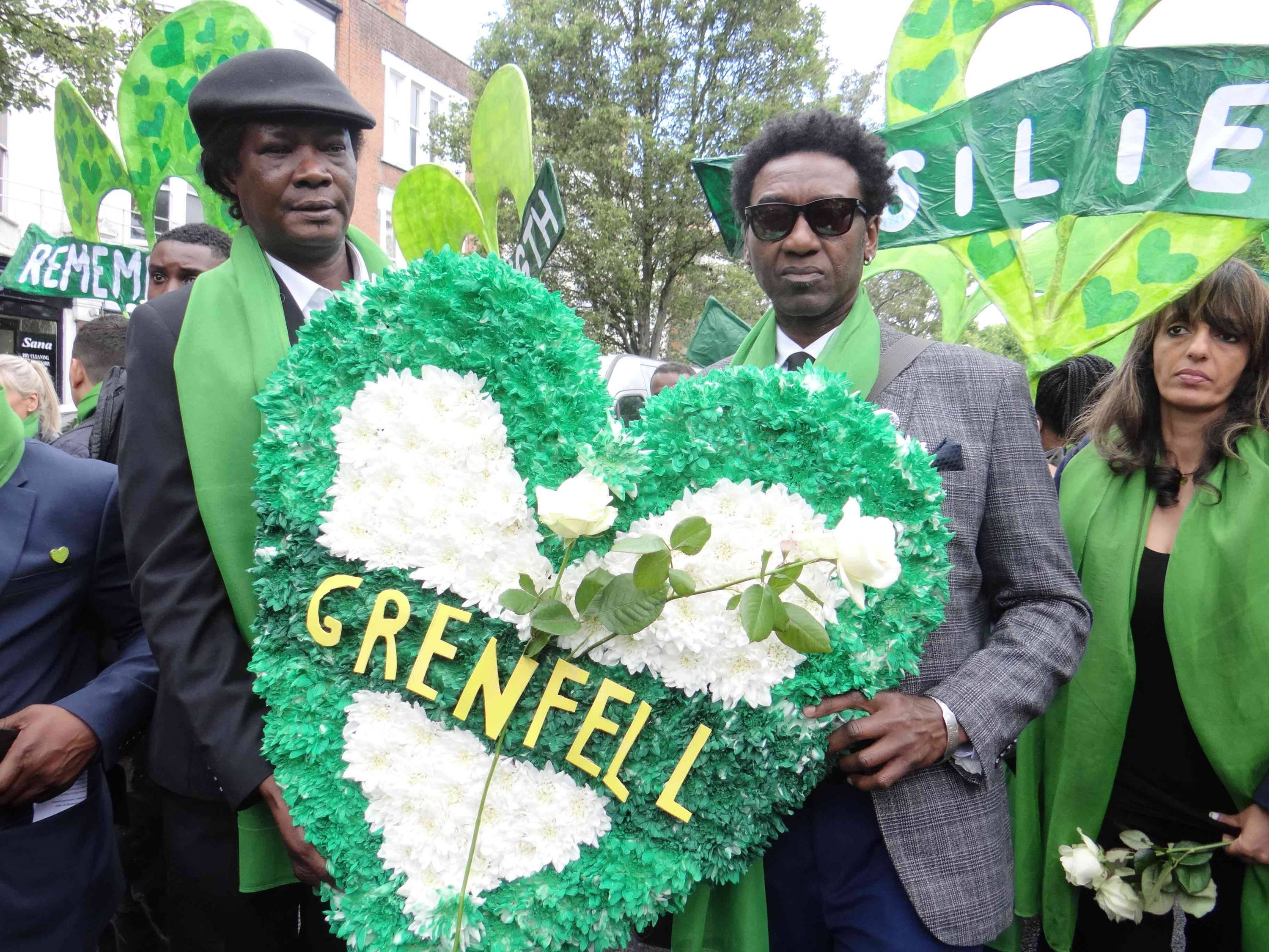 Two men holding a Grenfell floral tribute