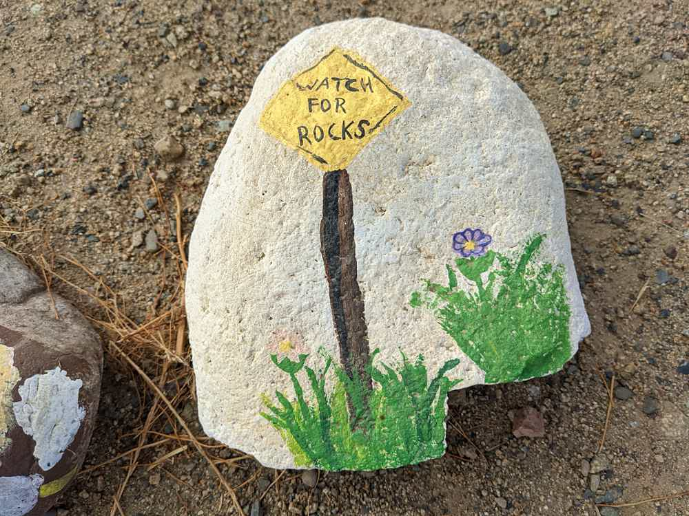 Rock with a sign painted on it saying Watch for Rocks at aLake Elsinore trail