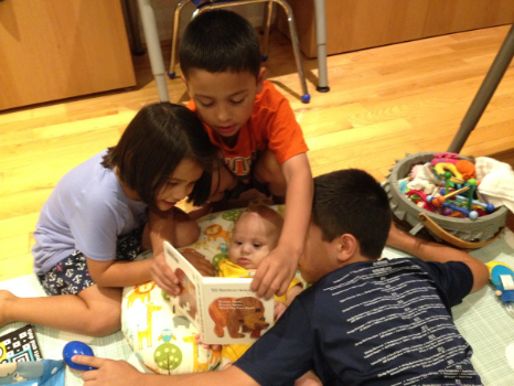 siblings reading story to baby