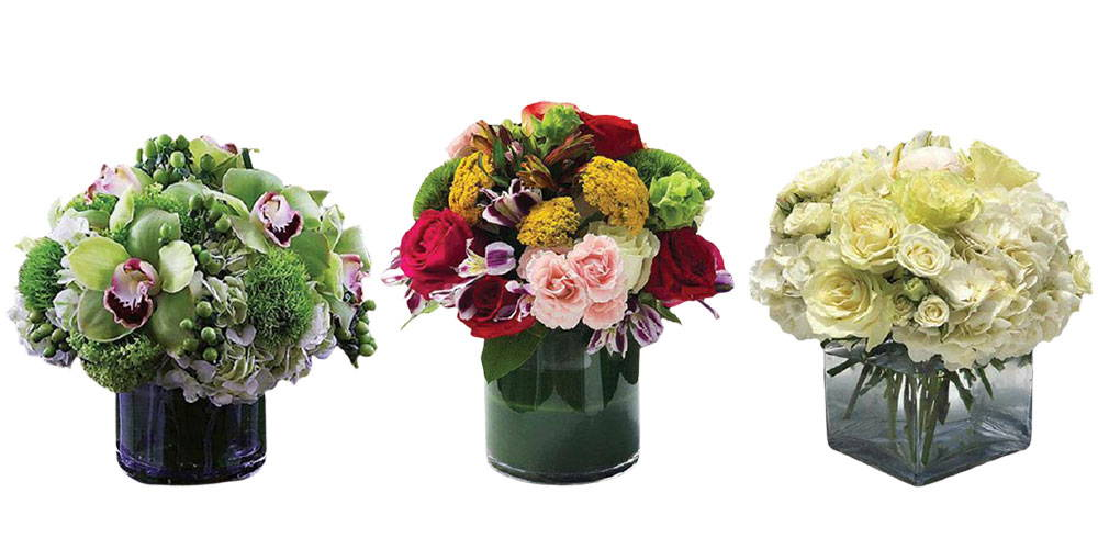 Picture of three short and compact flower arrangements in whites and greens