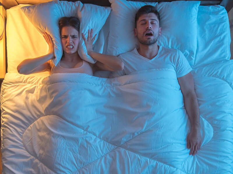couple in bed with a snoring partner