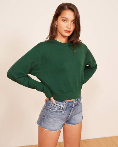 Front of woman wearing cropped denim shorts with a green organic cotton sweatshirt from sustainable fashion brand Reformation