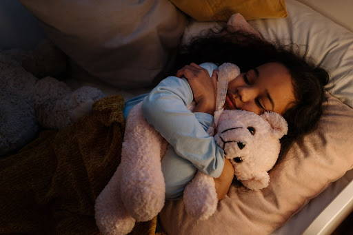 A little girl snuggled up with her teddy bear in bed, resting peacefully - Photo by cottonbro from Pexels