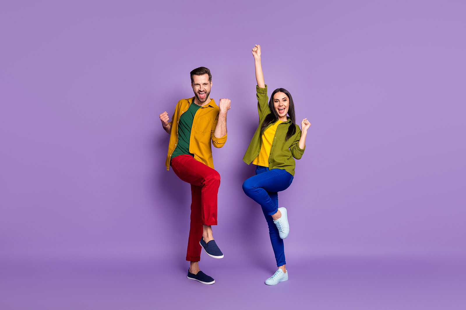 Image of an attractive white man and woman, both wearing colorful colors against a light purple background, both are smiling and have their hands up in the air in excitement.