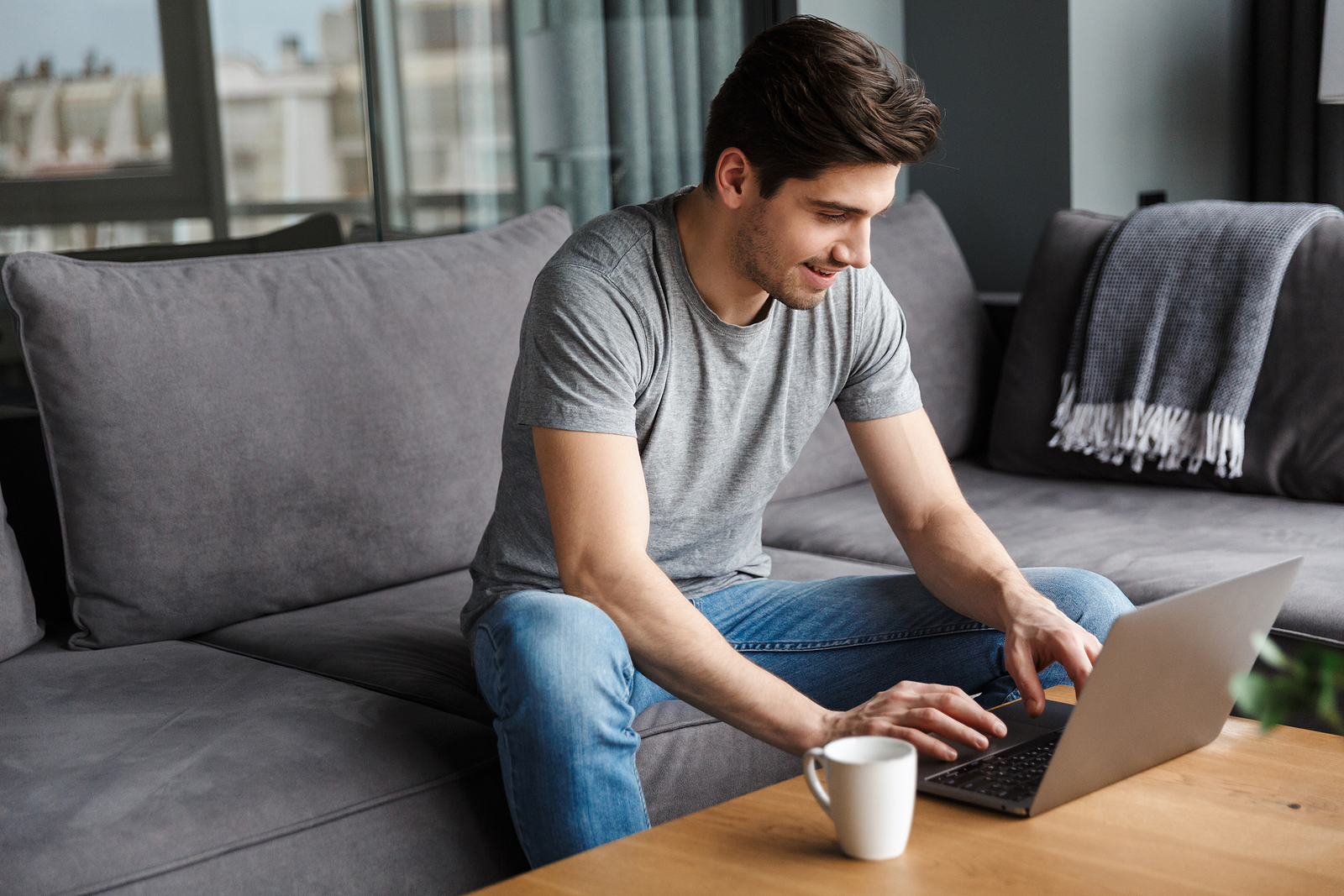 Photo of a white young man with a gray t shirt and jeans, sitting on a couch working on his laptop with a smile on his face.
