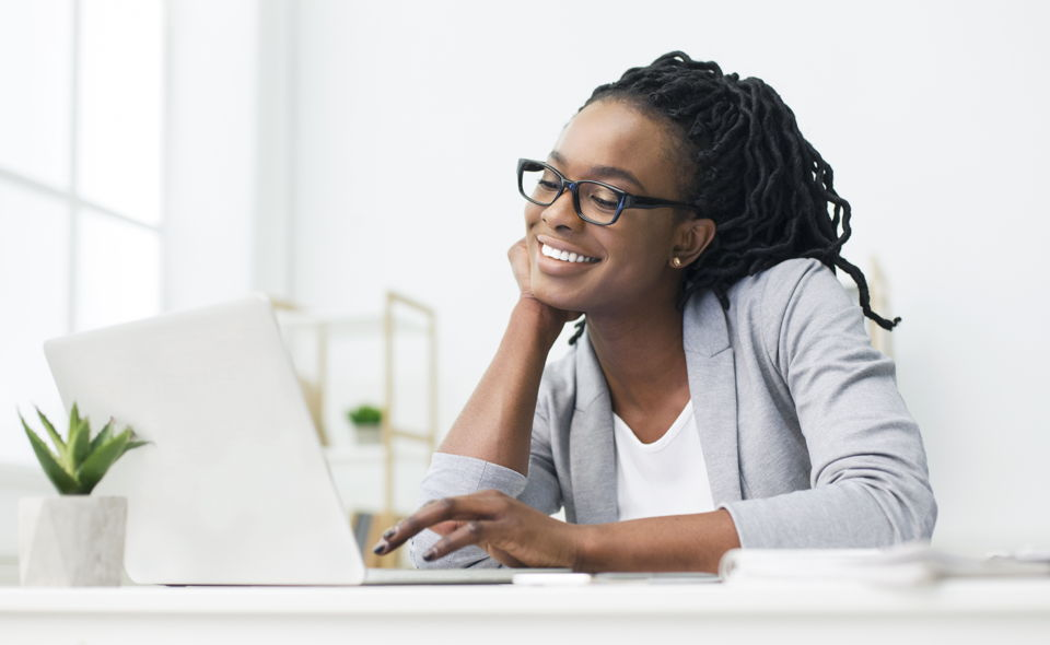 Smiling young woman working at laptop